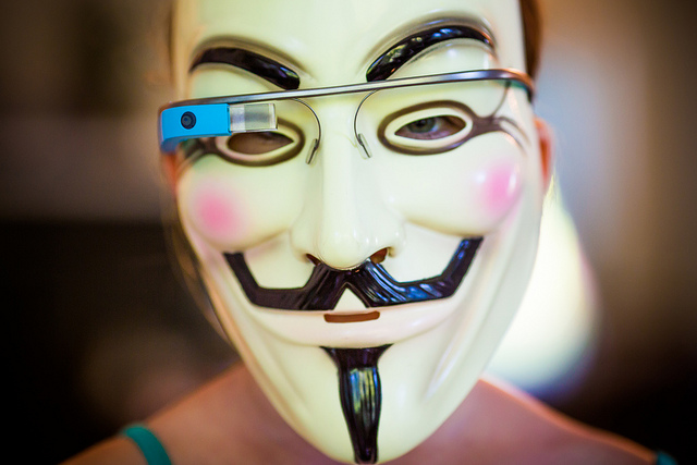 Closeup photograph of person wearing Google Glass wearable device over a Guy Fawkes mask